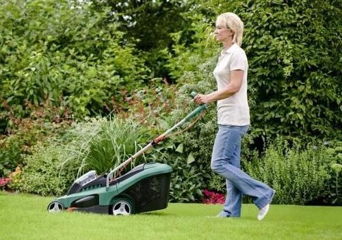 Jeune femme en train de tondre sa pelouse